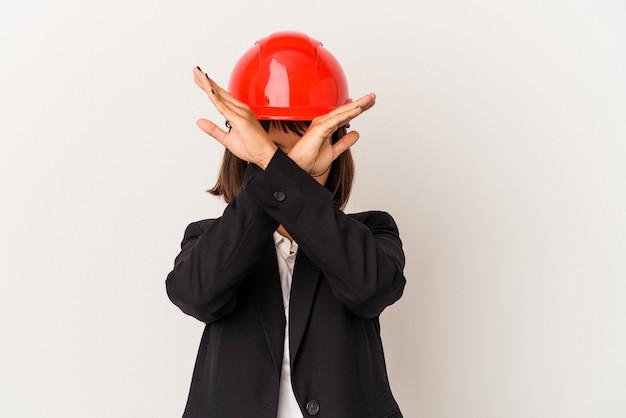 2つの腕を交差させたまま、白い背景で隔離の赤いヘルメットを持つ若い建築家の女性、否定の概念。
