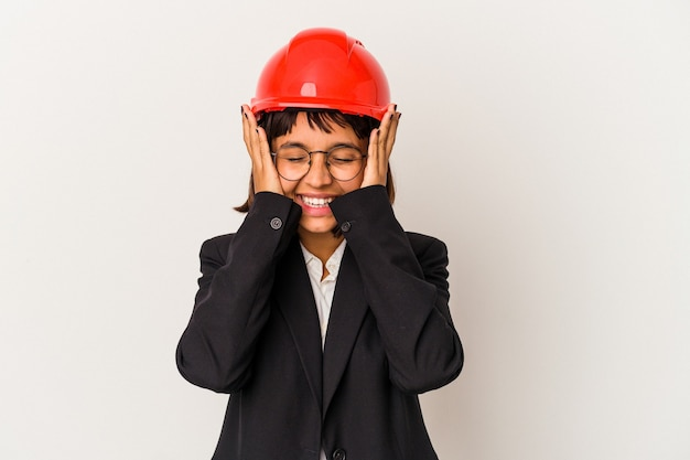 白い背景で隔離の赤いヘルメットを持つ若い建築家の女性は、頭に手を置いて喜んで笑います。幸福の概念。