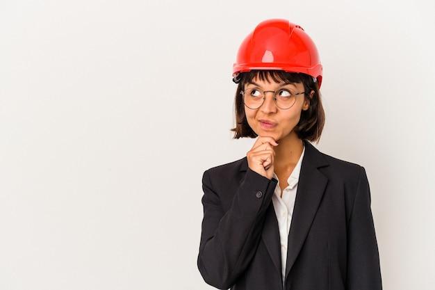 疑わしいと懐疑的な表現で横向きに見える白い背景に分離された赤いヘルメットを持つ若い建築家の女性。