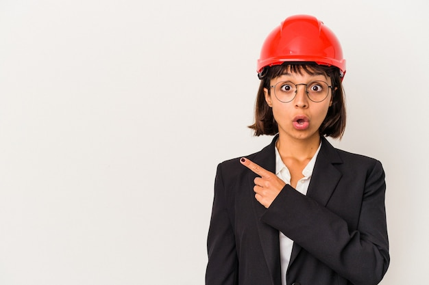 側面を指している白い背景で隔離の赤いヘルメットを持つ若い建築家の女性
