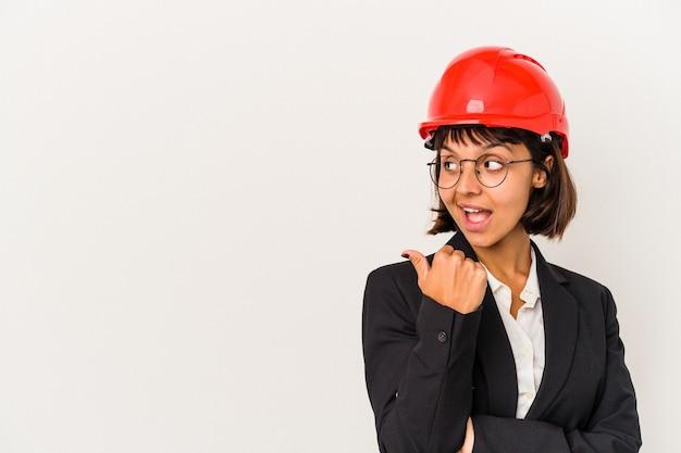 白い背景に分離された赤いヘルメットを持つ若い建築家の女性は、親指の指を離れて、笑って気楽にポイントします。
