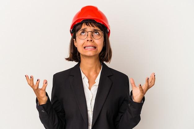 空に向かって叫び、見上げて、欲求不満の白い背景に分離された赤いヘルメットを持つ若い建築家の女性。