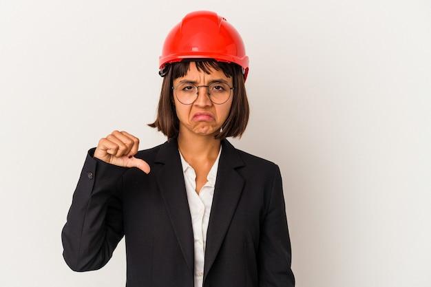 嫌いなジェスチャーを示す白い背景に分離された赤いヘルメットを持つ若い建築家の女性、親指を下に。不一致の概念。