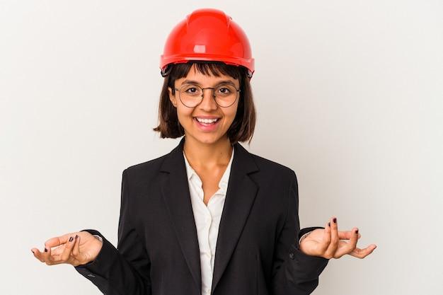歓迎の表現を示す白い背景で隔離の赤いヘルメットを持つ若い建築家の女性。