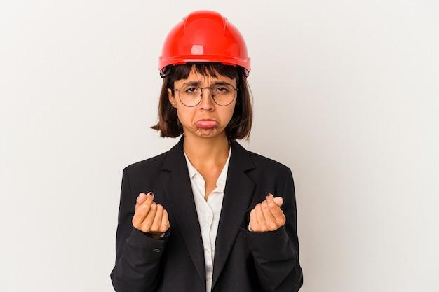 그녀는 돈이 없음을 보여주는 흰색 배경에 고립 된 빨간 헬멧을 가진 젊은 건축가 여자.