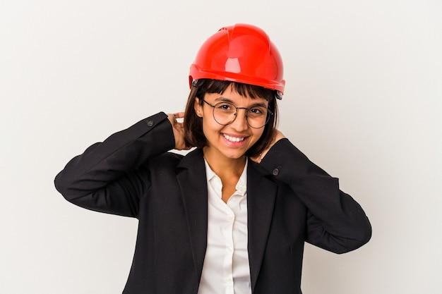 白い背景のストレッチ腕、リラックスした位置に分離された赤いヘルメットを持つ若い建築家の女性。