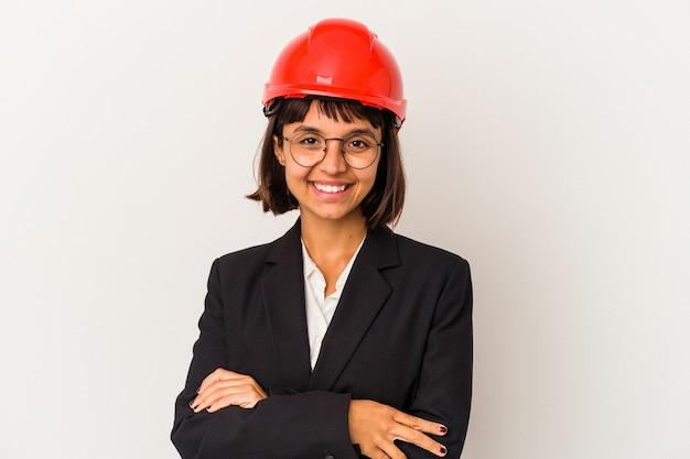 自信を持って、決意を持って腕を組んで、白い背景で隔離の赤いヘルメットを持つ若い建築家の女性。