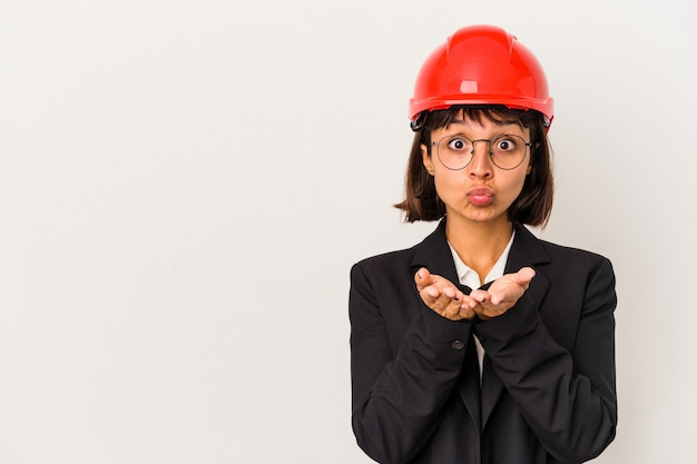 Young architect woman with red helmet isolated on white background folding lips and holding palms to send air kiss.