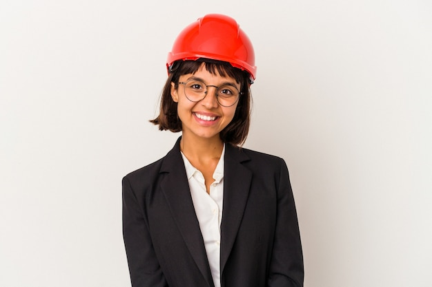 Young architect woman with red helmet isolated on white background happy, smiling and cheerful.