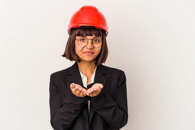 Young architect woman with red helmet isolated on white background holding something with palms, offering to camera.