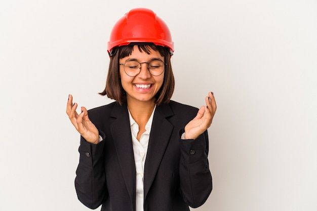 Young architect woman with red helmet isolated on white background joyful laughing a lot. happiness concept.