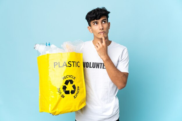 見上げている間疑いを持っているプラスチックでいっぱいのバッグを持っている若いアルゼンチン人男性