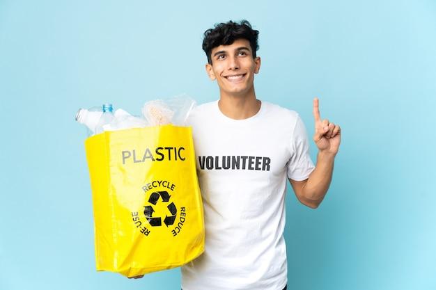 素晴らしいアイデアを指し示すプラスチックでいっぱいのバッグを持っている若いアルゼンチン人