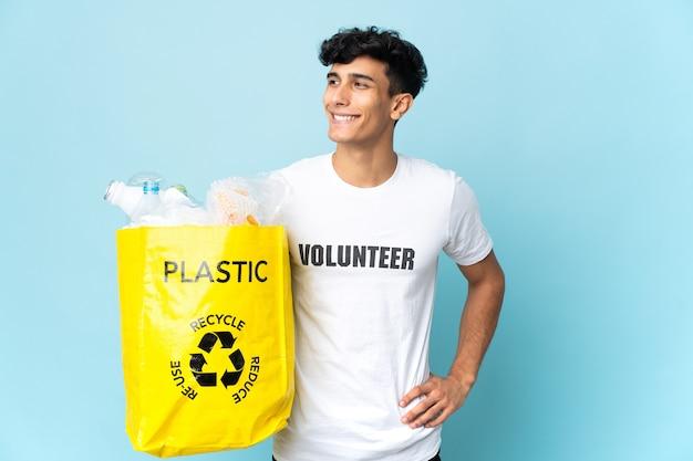 Молодой аргентинский мужчина держит сумку, полную пластика, позирует с руками на бедрах и улыбается