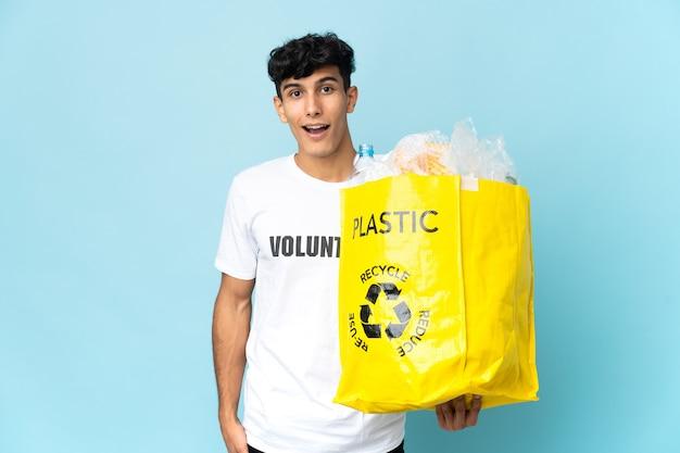 놀람과 충격을받은 표정으로 플라스틱으로 가득 찬 가방을 들고 젊은 아르헨티나 남자
