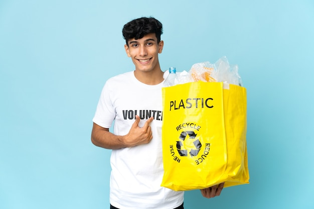 Young argentinian man holding a bag full of plastic with surprise facial expression
