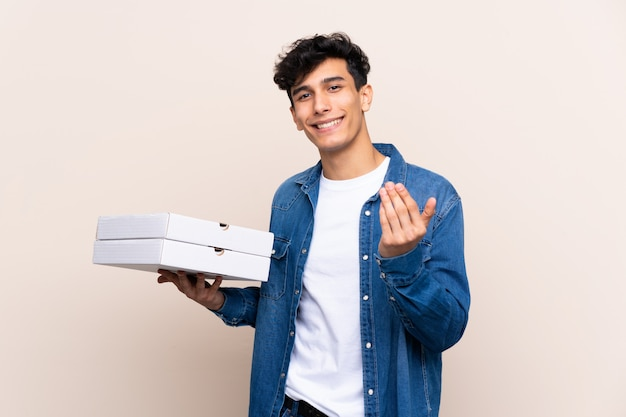 Young argentinian man holding pizzas over isolated wall inviting to come with hand. happy that you came