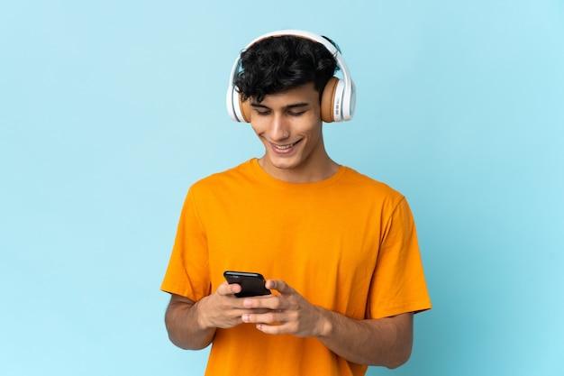 音楽を聴き、モバイルを探している背景に孤立した若いアルゼンチン人