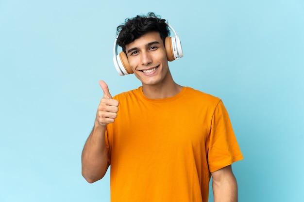音楽を聴いて、親指を立てて背景に孤立した若いアルゼンチン人