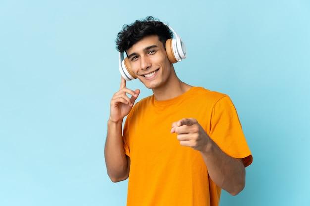 音楽を聴き、正面を指して壁に孤立した若いアルゼンチン人