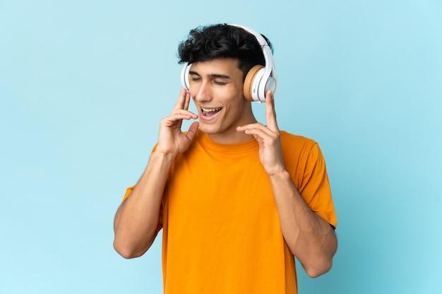 Молодой аргентинский мужчина изолирован на стене, слушает музыку и поет