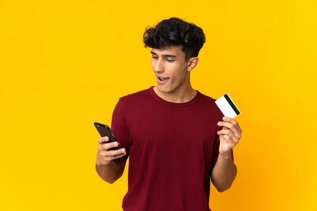 Молодой аргентинский мужчина, изолированные на желтом фоне, покупает с мобильного с помощью кредитной карты