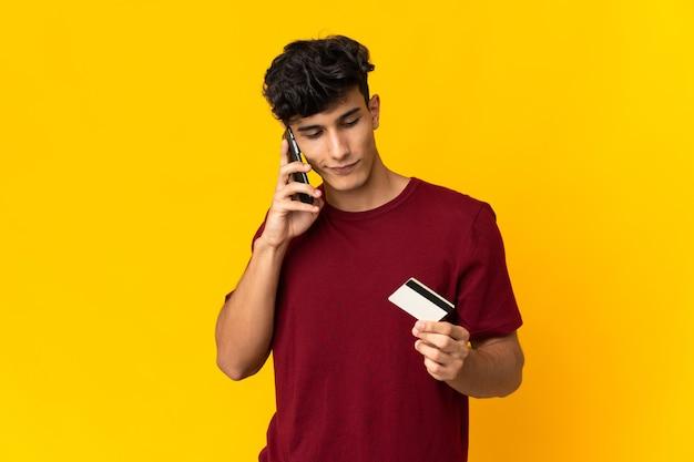 Молодой аргентинский мужчина, изолированные на желтом фоне, покупает с мобильного телефона с помощью кредитной карты