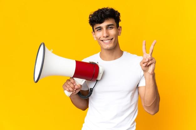 Молодой аргентинский мужчина, изолированные на желтом фоне, держит мегафон и улыбается и показывает знак победы