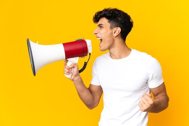 Молодой аргентинский мужчина, изолированный на желтом фоне, кричит в мегафон, чтобы объявить что-то в боковом положении