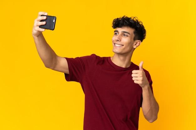 Молодой аргентинский мужчина изолирован на желтой стене, делая селфи с мобильного телефона