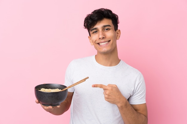Young argentinian man over isolated white wall and pointing it while holding a bowl of noodles with chopsticks