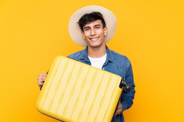 Young argentinian man over isolated yellow background in vacation with travel suitcase and a hat