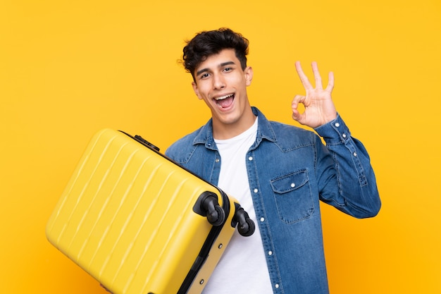 Young argentinian man over isolated yellow background in vacation with travel suitcase and making ok sign