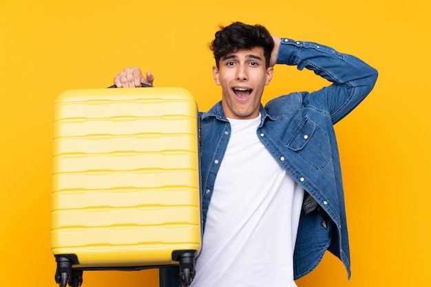 Young argentinian man over isolated yellow background in vacation with travel suitcase and surprised