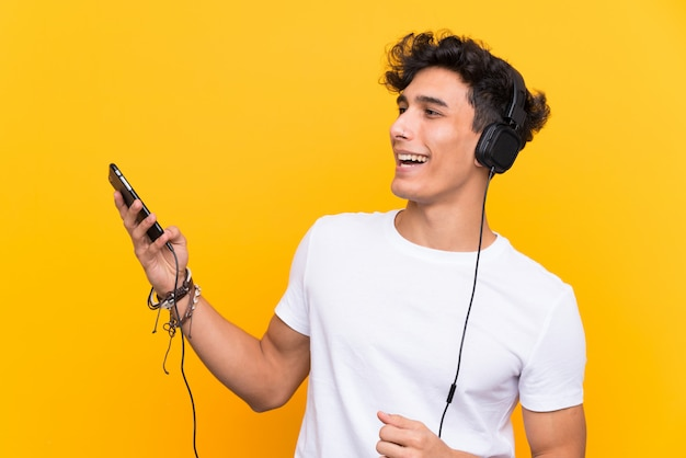 Young argentinian man listening music with a mobile over isolated yellow wall
