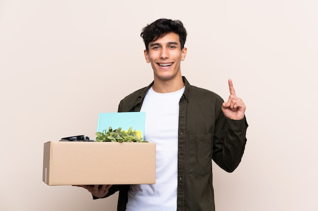 Young argentinian man moving in new home over isolated pointing up a great idea