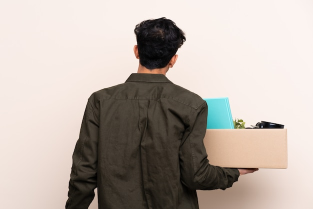 Young argentinian man moving in new home over isolated wall in back position
