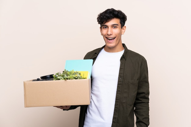 Young argentinian man moving in new home over isolated wall with surprise and shocked facial expression