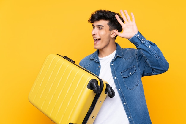 Young argentinian man in vacation with travel suitcase and saluting