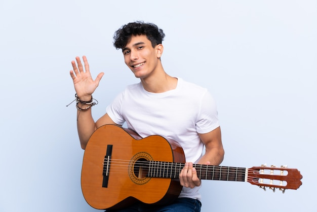 Young argentinian man with guitar over isolated blue wall saluting with hand with happy expression