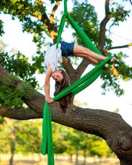 Молодой arial гимнастический атлет и вид на дерево