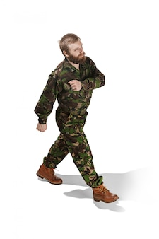 Young army soldier wearing camouflage uniform going isolated on white studio