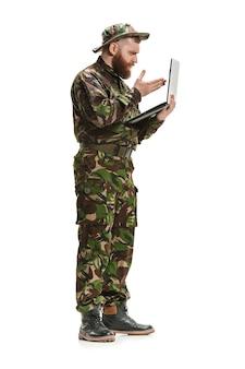 ノートパソコンとフルレングスの白いスタジオ背景に分離された迷彩服を着ている若い陸軍兵士。軍事、兵士、軍のコンセプトです。プロフェッショナル、コミュニケーション、コネクテッドピープルのコンセプト