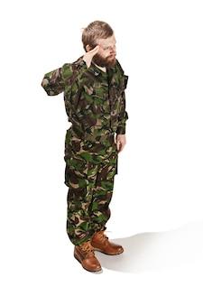 迷彩服を着て立っているとフルレングスの白いスタジオ背景に分離された敬礼を身に着けている若い軍の兵士。若い白人モデル。軍事、兵士、軍のコンセプトです。専門的な概念