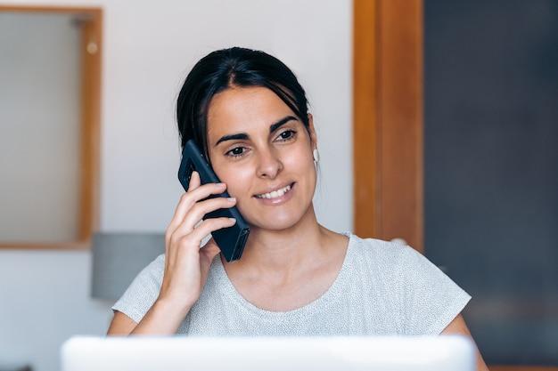 自宅で仕事をし、電話で話している若い職人の女性。彼女は机に座っています。
