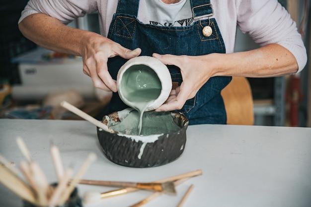 Молодой ремесленник женщина работает с ее рукой кусок керамического фокуса под рукой