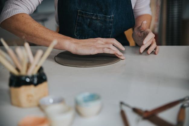 Молодой ремесленник женщина, работающая с ее рукой кусок керамического внимания на руках