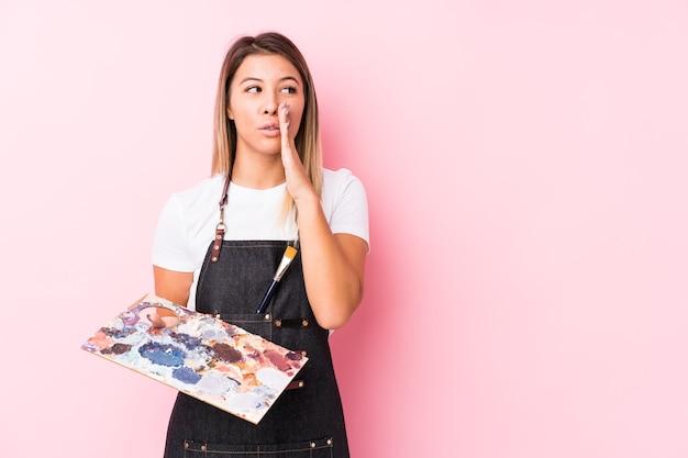 Молодая кавказская женщина-художник, держащая изолированную палитру, говорит секретные горячие новости о торможении и смотрит в сторону