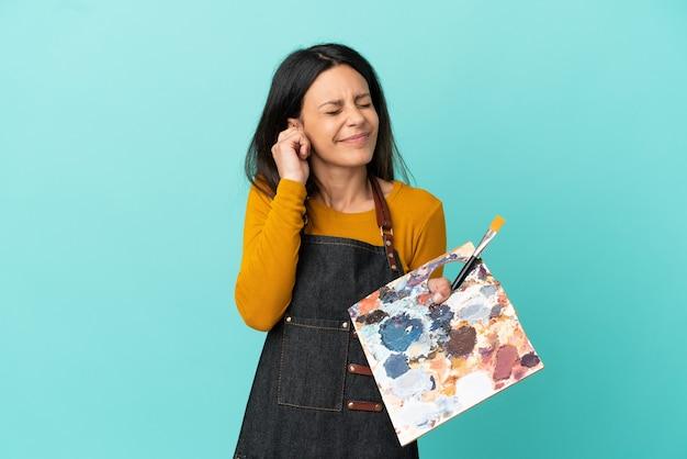 Молодая кавказская женщина-художник, держащая палитру, изолированную на синем фоне, разочарована и закрывает уши