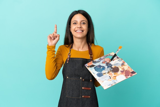 Молодая кавказская женщина-художник, держащая палитру, изолированную на синем фоне, показывает и поднимает палец в знак лучших